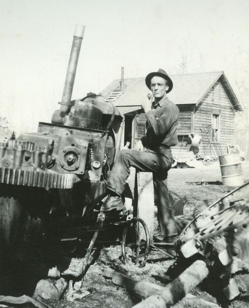 Gus working on tractor with Dale in background 1946 2
